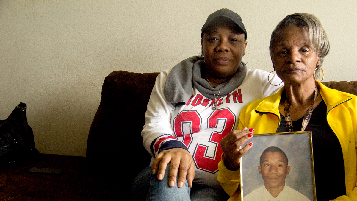 Robert Owens, 15, was fatally shot in Chicago in 1998. His sister Sharon Burgman-Owens, left, and mother Seonia Owens, right, hold a photo of Robert in their Kenosha home. (WBEZ / Miles Bryan)
