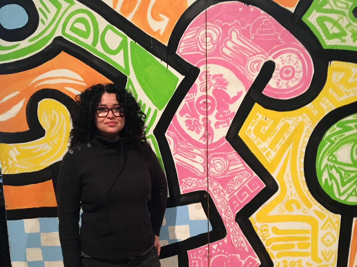 Sandra Antongiorgi stands in front of the panel she painted on the mural, which is pink with white Aztec and Mayan symbols. (Carrie Shepherd/WBEZ)