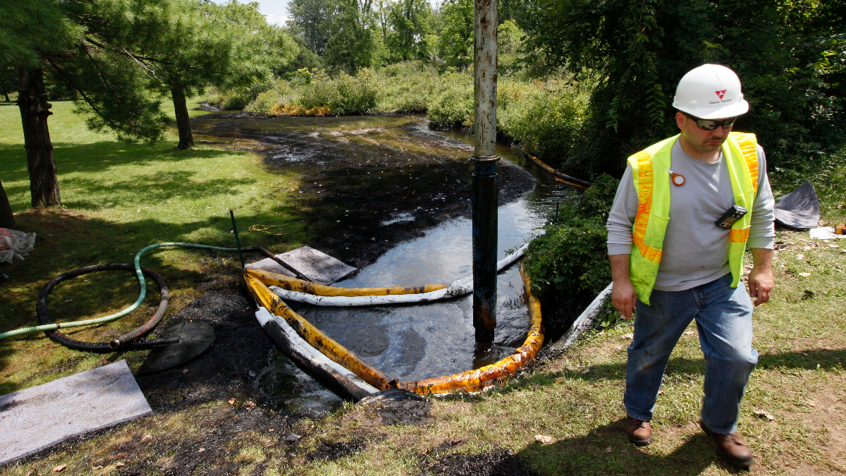A worker monitors the water in Talmadge Creek near the Kalamazoo River in Marshall Township, Mich., as oil from a ruptured pipeline, owned by Enbridge Inc., is vacuumed out the water on July 29, 2010. (AP Photo/Al Goldis)