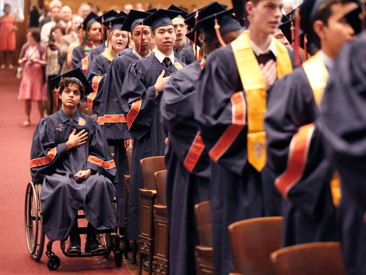 Jonathan Annicks and fellow graduates listen to the national anthem during their high school graduation ceremony on June 13, 2016 in Chicago. His family's support and his desire keep him strong. 'If I crumble, then I feel like everything around me would, too. ... I'm just living my life as I would normally and that's keeping everyone around me sane.' (AP Photo/Charles Rex Arbogast).