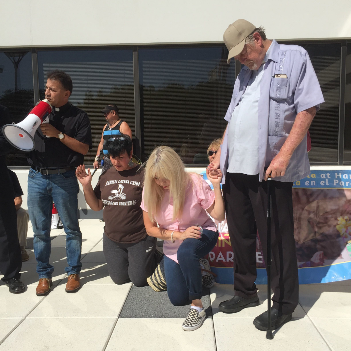 Rev. Jose Landaverde leads protesters in a closing prayer after Park Ridge police told protesters to leave. Rev. Emma Lozano is kneeling and holding her husband's hand, Rev. Walter Coleman.