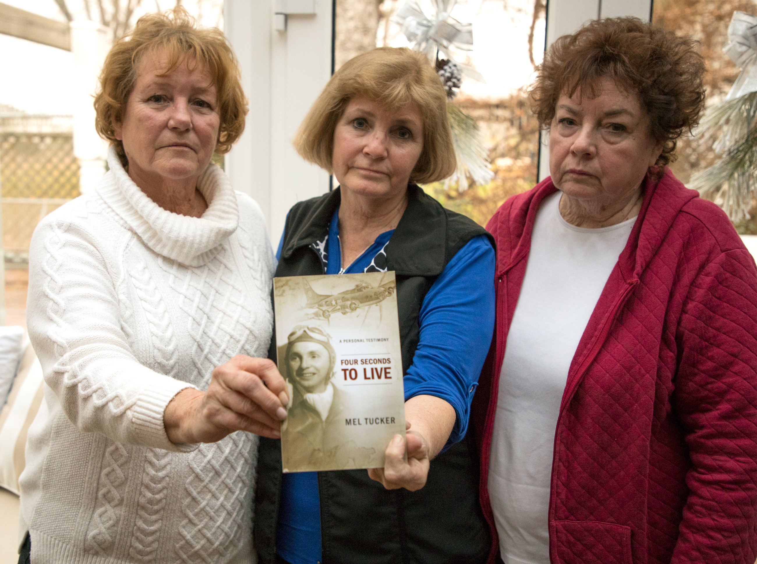 The daughters of former World War II Army veteran Melvin Tucker — Diane McHatton, Barb Harrison, and Jeanne Smith — display their father's autobiography that outlined life as a prisoner of war. (Andrew Gill/WBEZ)