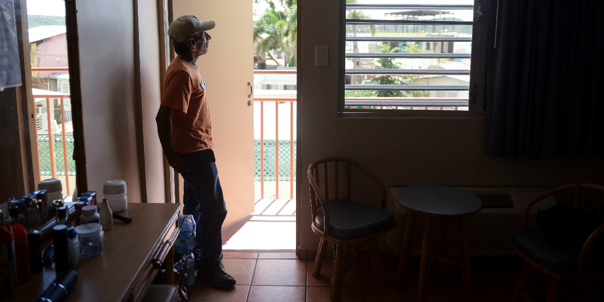 In this Feb. 26, 2018 photo, 53-year-old retiree Fernando Muniz looks out from his hotel room, where he has taken refuge for months after Hurricane Maria caused damage to his San Juan residence, in Cabo Rojo, Puerto Rico. (AP Photo/Carlos Giusti).