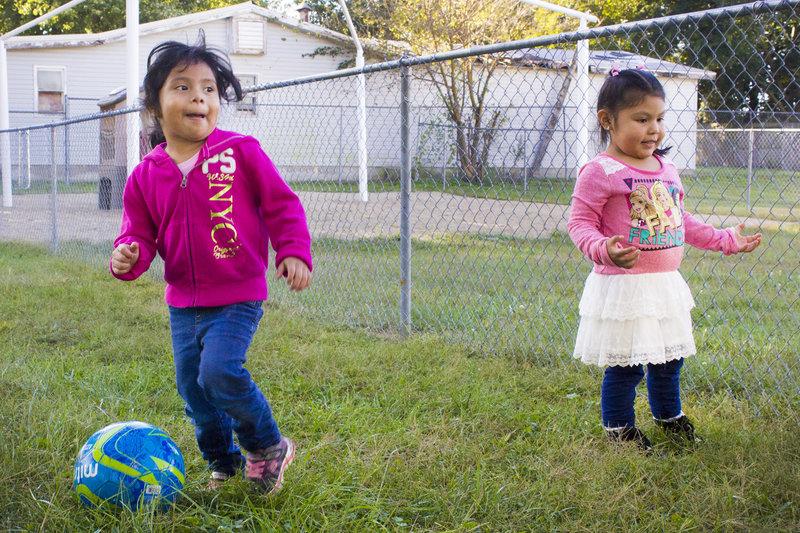 Ximena (left) kicks a soccer ball with Yareli at the Indiana Migrant Preschool Center.