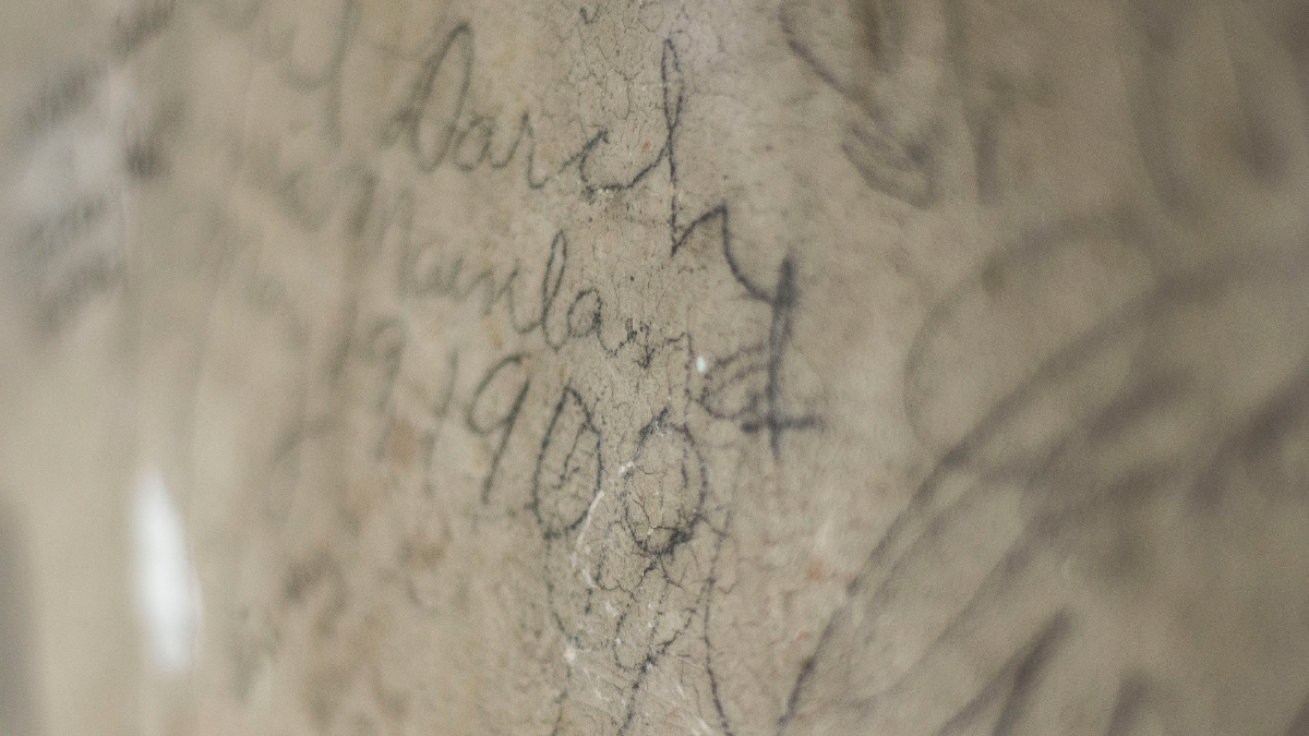 When Wheaton students get engaged, they climb to the top of the bell tower in Blanchard Hall and sign their names. Most of the oldest names were lost or covered up, but this signature dates to 1900. (Jason Marck/WBEZ)