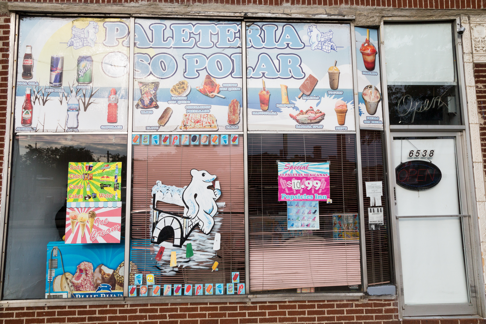Colorful posters and stickers cover the exterior of La Polar's Clark Street storefront. (WBEZ/Shawn Allee)