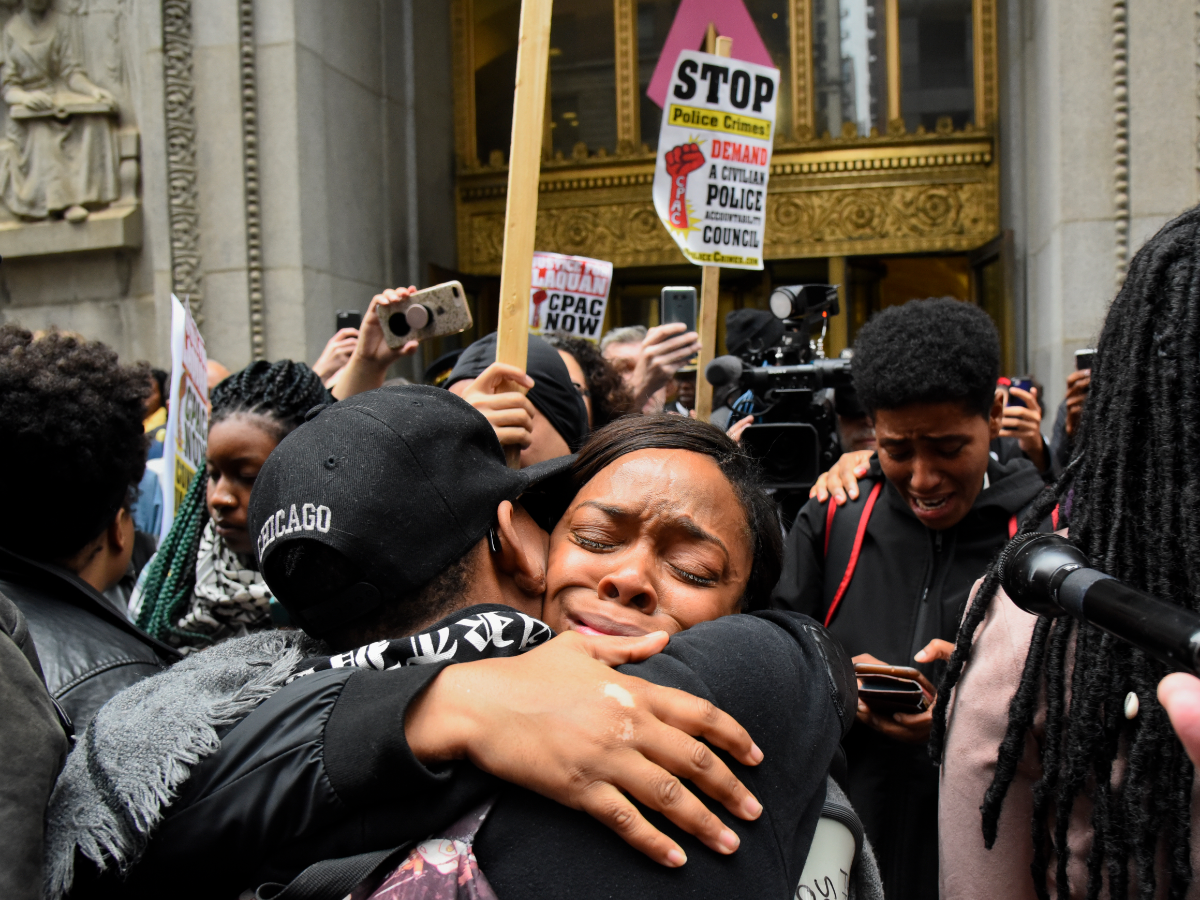Friday, Oct 5, 2018: People embrace as they listen intently to live streamed coverage of a jury's conviction of Chicago police Officer Jason Van Dyke of second-degree murder in the 2014 shooting of teenager Laquan McDonald. Activist groups did not threaten to riot. (Matt Marton/AP)