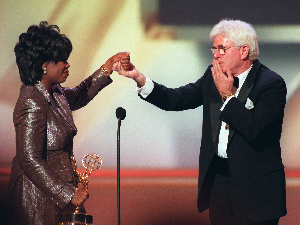 Phil Donahue blows a kiss to Oprah Winfrey as she presents him with a Lifetime Achievement Award at the 23rd Annual Daytime Emmy Awards on May 22, 1996. (AP Photo/Ron Frehm)