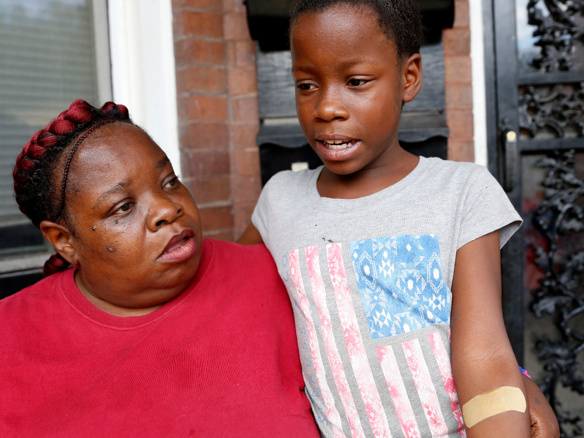 Ten-year-old Etyra Ruffin, right, shows her injured arm as she speaks next to her grandmother, Yvette, Thursday, Sept. 1, 2016, in Chicago. Chicago saw its deadliest month in two decades in August, recording 90 homicides for the month, the city's police department said Thursday. Chicago police say Etyra injured her arm as she fled from another instance of gun violence in the city. (Tae-Gyun Kim/AP Photo)