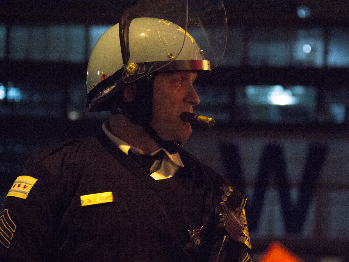A Chicago police officer on horseback smokes a cigar outside Wrigley Field during Game 7 of the World Series. (Andrew Gill/WBEZ)