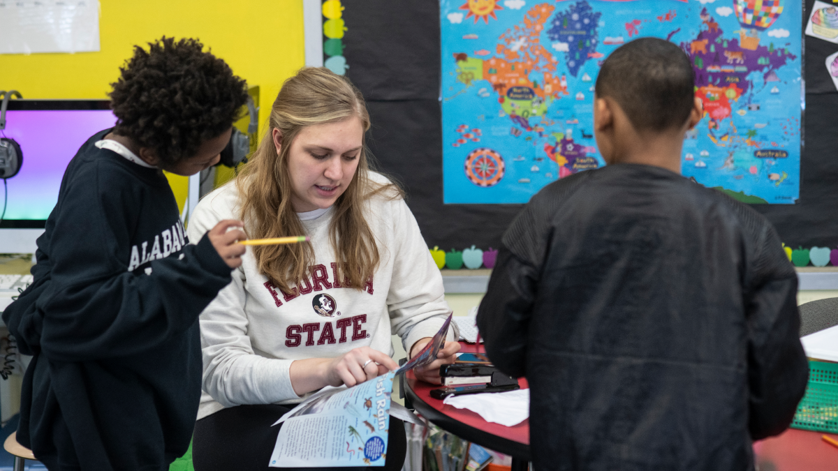 During Rahm Emanuel's tenure as mayor, test scores and graduation rates rose but the mayor also oversaw the first teachers strike in 25 years and the closing of 50 schools. Here, a teacher at Shoesmith Elementary School works with a student.