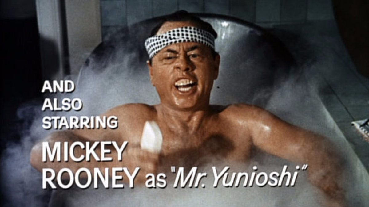 Mickey Rooney starred as Mr. Yunioshi, Audrey Hepburn's irascible Asian neighbor, in the 1961 film 'Breakfast at Tiffany's'. Contemporary reviews of the film typically condemn Rooney's portrayal as a toxic caricature.  (Screenshot from trailer/Paramount Pictures/Wikimedia Commons)