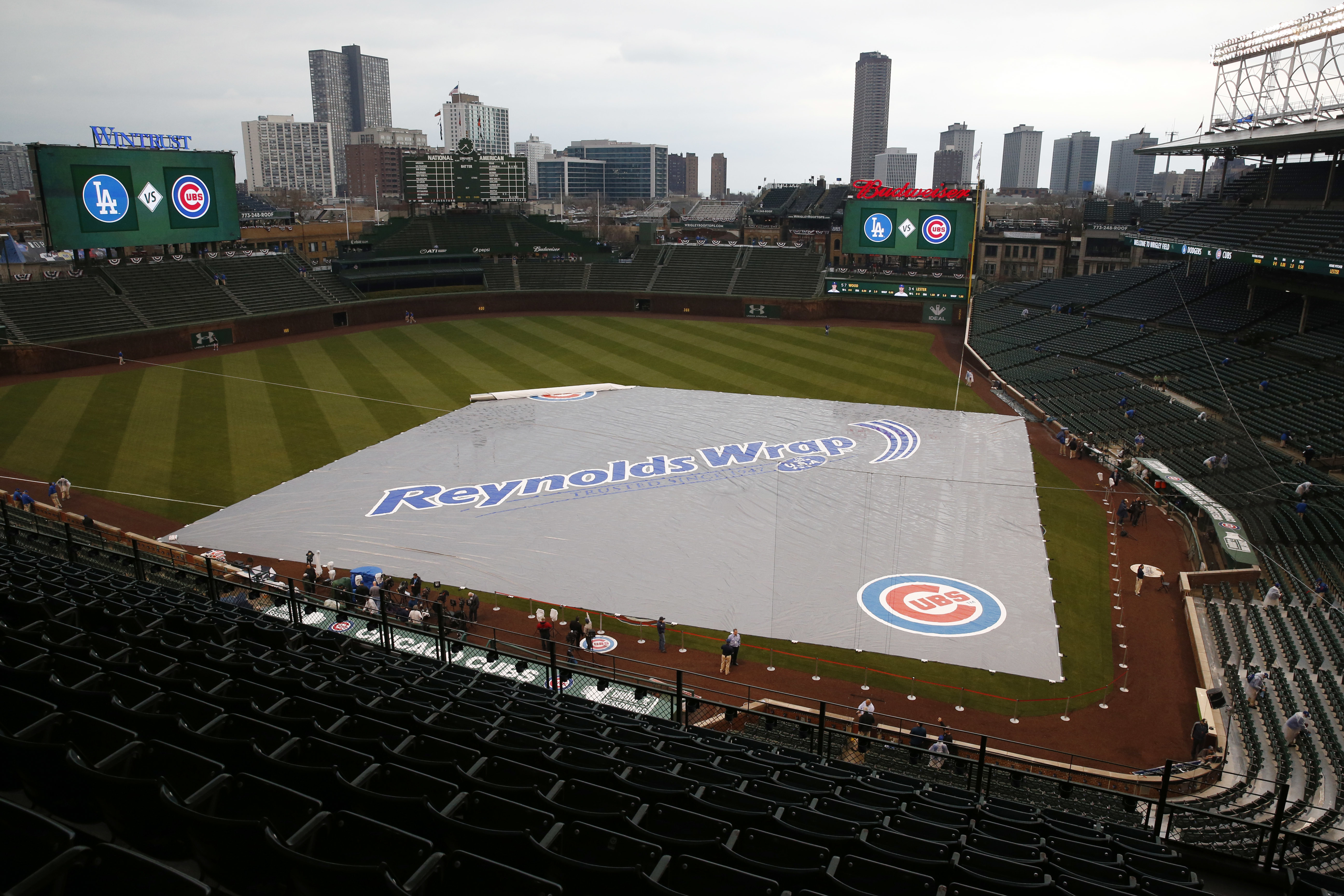 A tarp covers the field at Wrigley amid early afternoon rainstorms on home opening day, Monday, April 10, 2017. The bullpens, formerly located down the first-base and third-base lines, were moved beneath the bleachers during the offseason.  (AP Photo/Nam Y. Huh)