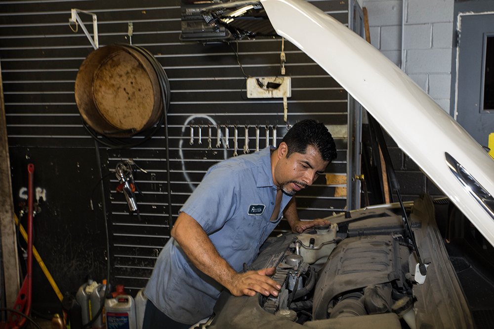 Fernando Serna attends to a car in his autobody shop on Pulaski Road in Ashburn. (Courtesy Jason Schumer/City Bureau)