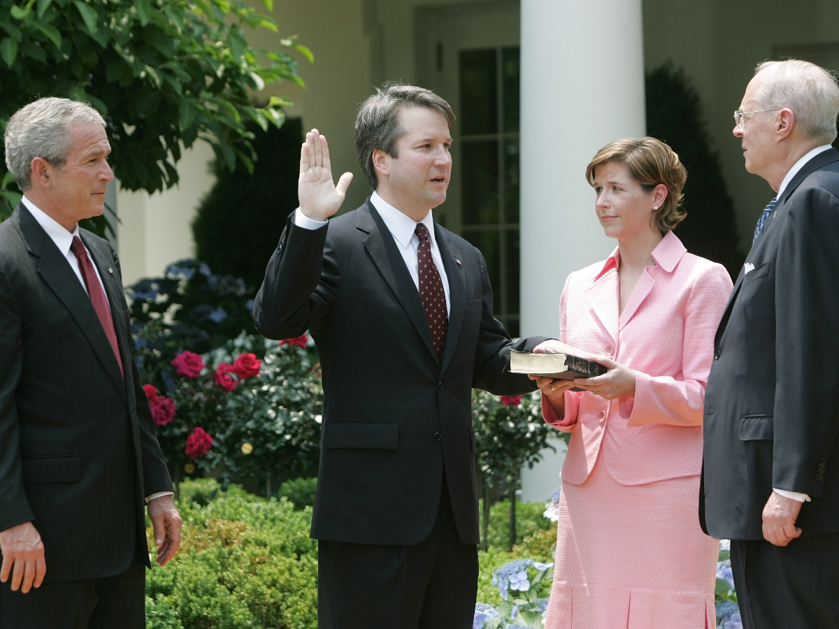 President George W. Bush watches the swearing-in of Brett Kavanaugh as Judge for the U.S. Court of Appeals for the District of Columbia by U.S. Supreme Court Associate Justice Anthony M. Kennedy, far right, on June 1, 2006. Holding the Bible is Kavanaugh's wife Ashley Kavanaugh. (AP Photo/Pablo Martinez Monsivais).