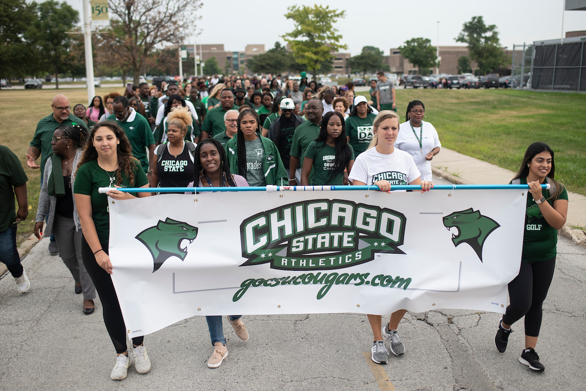 Members of the Chicago State's golf team and their coach Angela Dehning lead a group of CSU athletes and their coaches toward 99th Street during the August back-to-school parade. The negative publicity around the school in recent years helped drive down enrollment by 3,700 students. (Marc C. Monaghan for WBEZ)