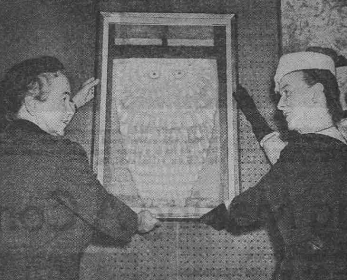 """Mrs. C. Phillip Miller and Mrs. Solomon B. Smith hang a contemporary painting titled, """"The Owl,"""" in preparation for the spring 1959 sale. (Courtesy Chicago Sun-Times)"""
