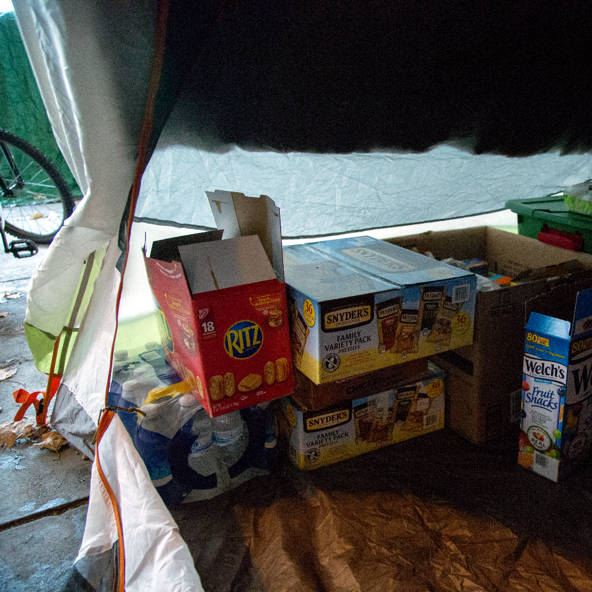 Non-perishable supplies are kept in a storage tent secured with a padlock in the Wilson Avenue tent city. (Andrew Gill/WBEZ)