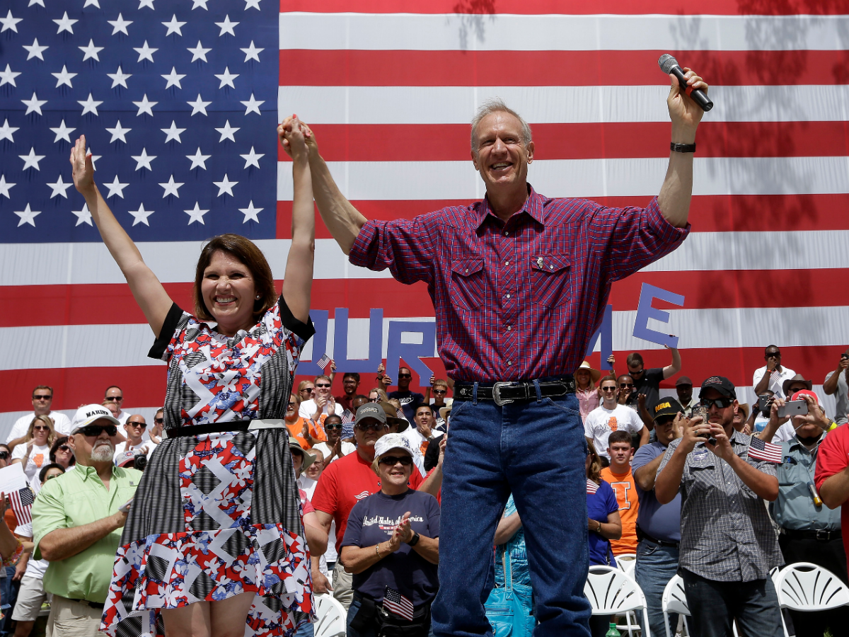 Gov. Bruce Rauner and Lt. Gov. Evelyn Sanguinetti wave to supporters during a Govenor's Day rally at the Illinois State Fair in 2018. (Seth Perlman/AP Photo)
