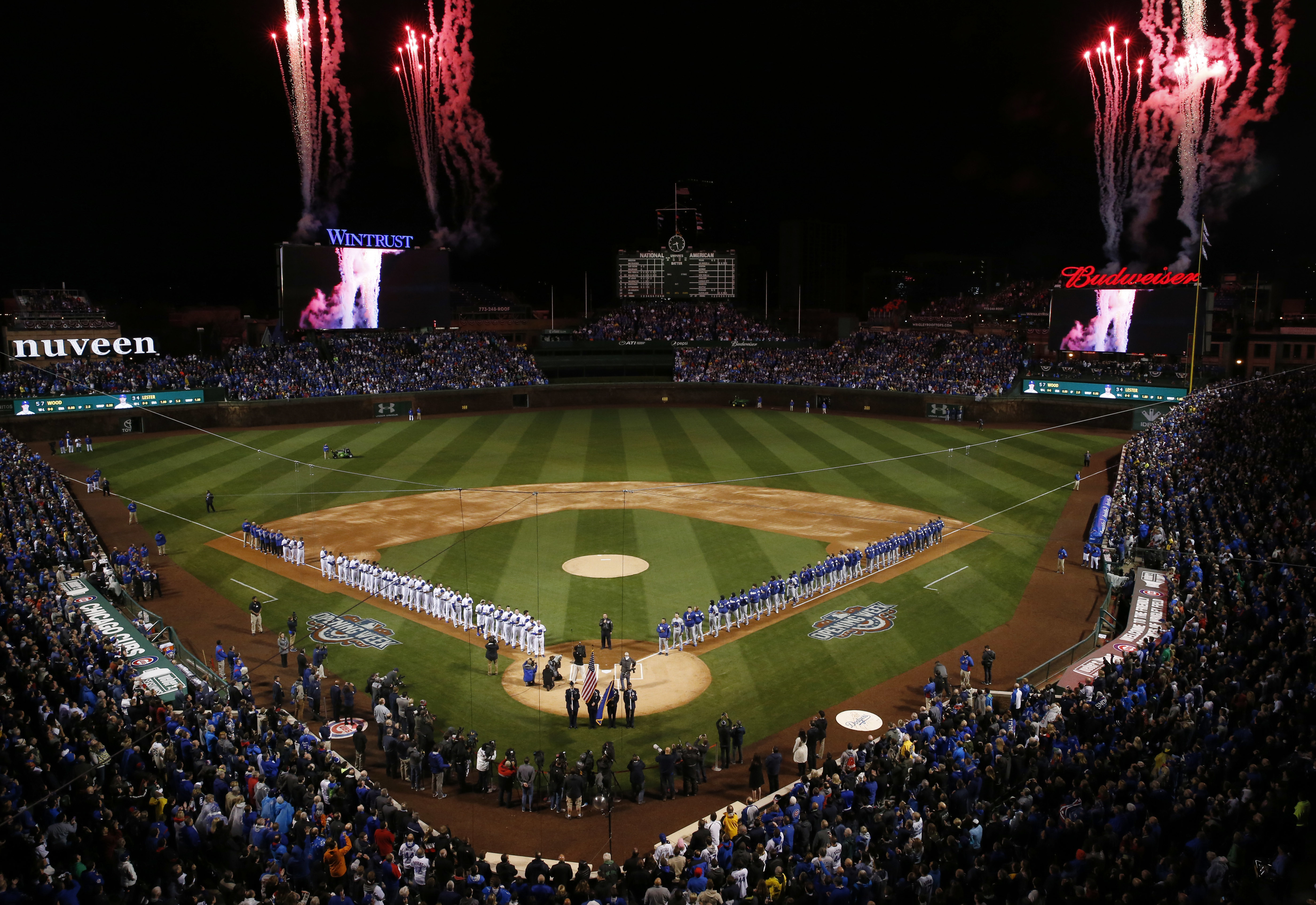 Fans and players stand as they watch fireworks during the national anthem in the home opening ceremonies. (AP Photo/Nam Y. Huh)
