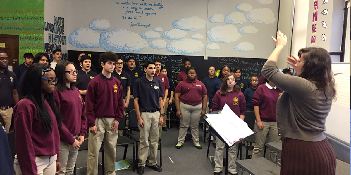 Teacher Kelsey Tortorice leads a student choir at UIC College Prep in Chicago. (WBEZ/Becky Vevea)