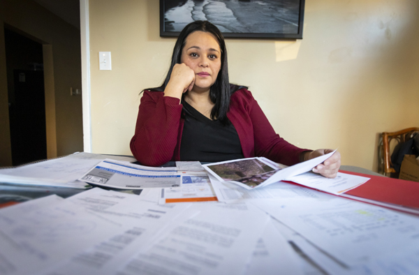 Sandra Botello, 42, sits at her dinning room table with a pile of paperwork related to the seizure and eventual sale of her car to a private tow company by the city of Chicago on January 5, 2018. (Manuel Martinez/WBEZ)