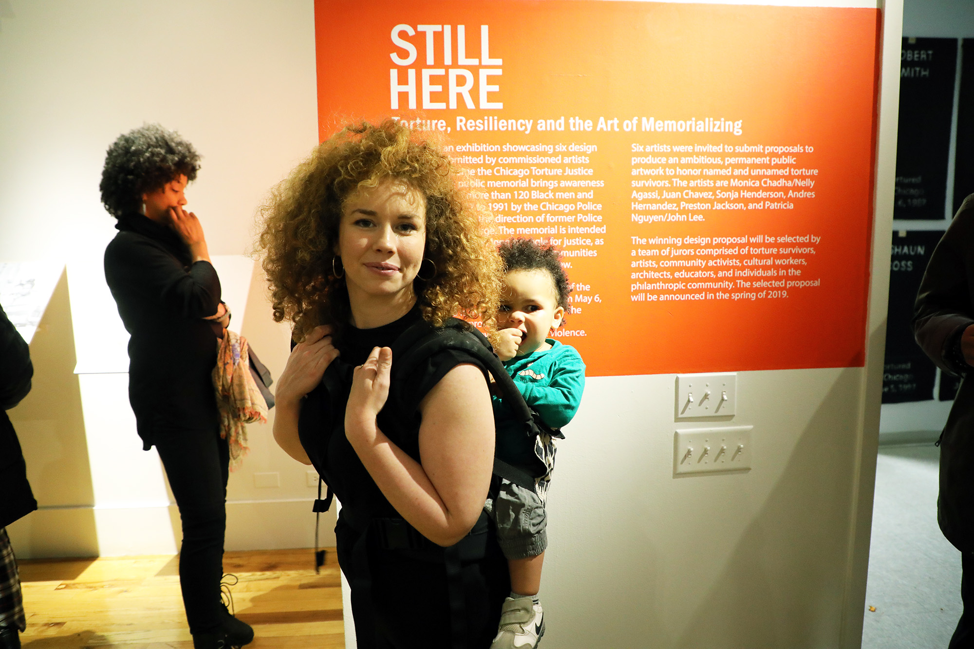 Co-curator Hannah Jasper stands near the exhibit's entrance with her son.