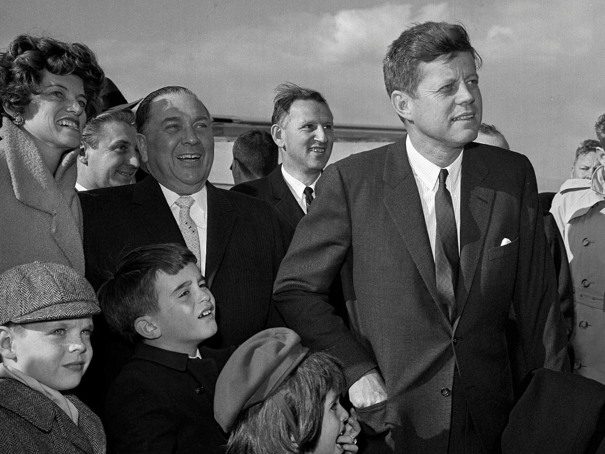 President John F. Kennedy stands during a welcoming ceremony at Chicago's O'Hare Airport as Mayor Richard Daley looks on, second from left, with Kennedy's sister Eunice Kennedy Shriver, at left, on April 28, 1961. (AP Photo)