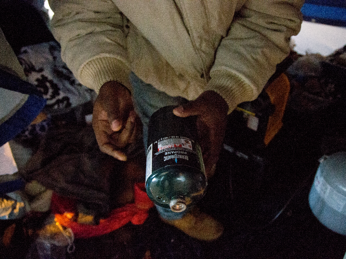 William Brown, one of the house elders, shows the propane tanks community members rely on for heat in the Wilson Avenue tent city. (Andrew Gill/WBEZ)