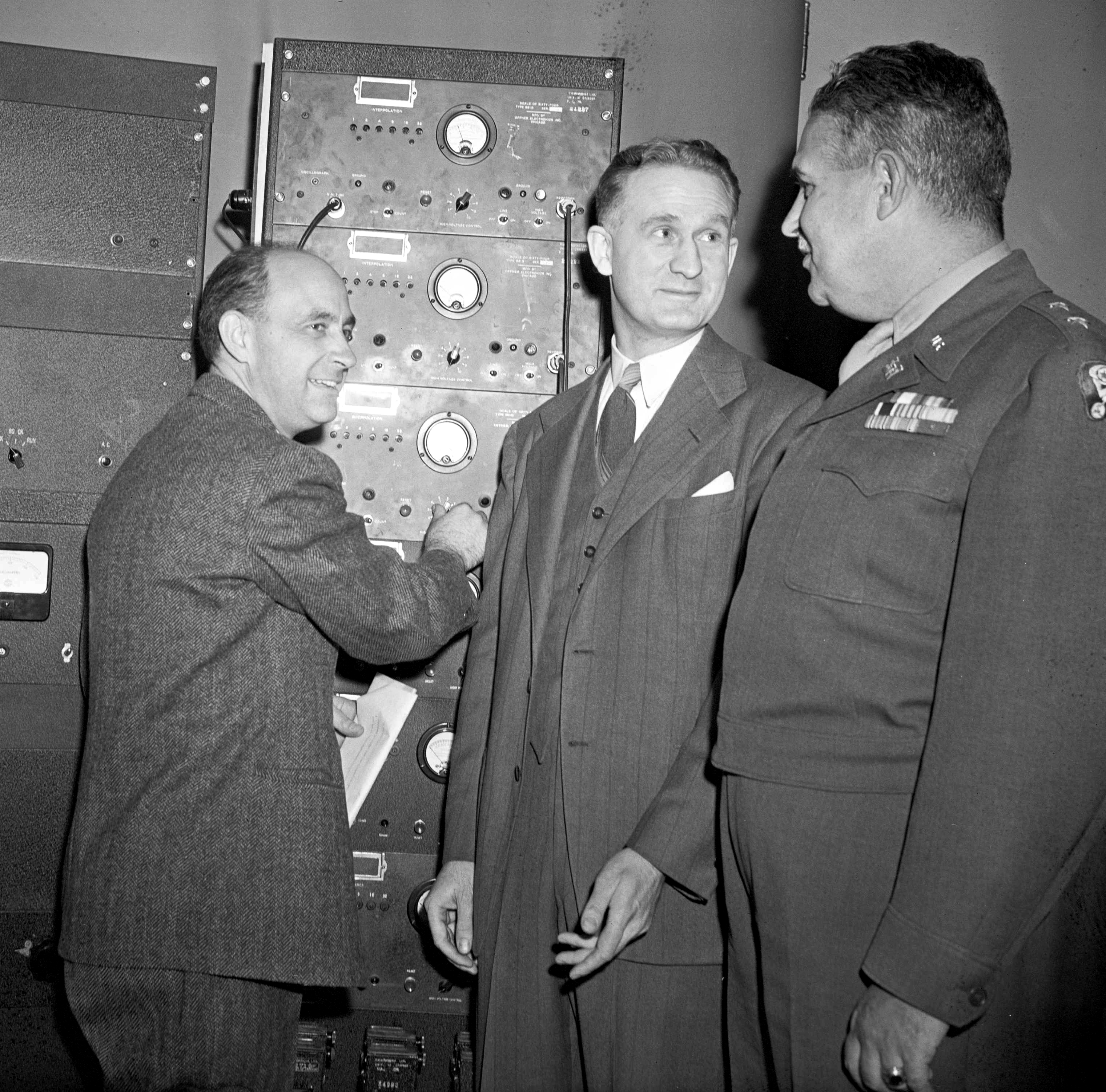Dr. Enrico Fermi, left, Dr. Walter H. Zinn, center, and Maj. Gen. Leslie R. Groves, head of the Manhattan Engineering Project, look over a nuclear instrument during a reunion in Chicago, Ill., Dec. 2, 1946, the fourth anniversary of the first demonstration that atomic energy could be released and controlled. (AP Photo/Charles Knoblock)