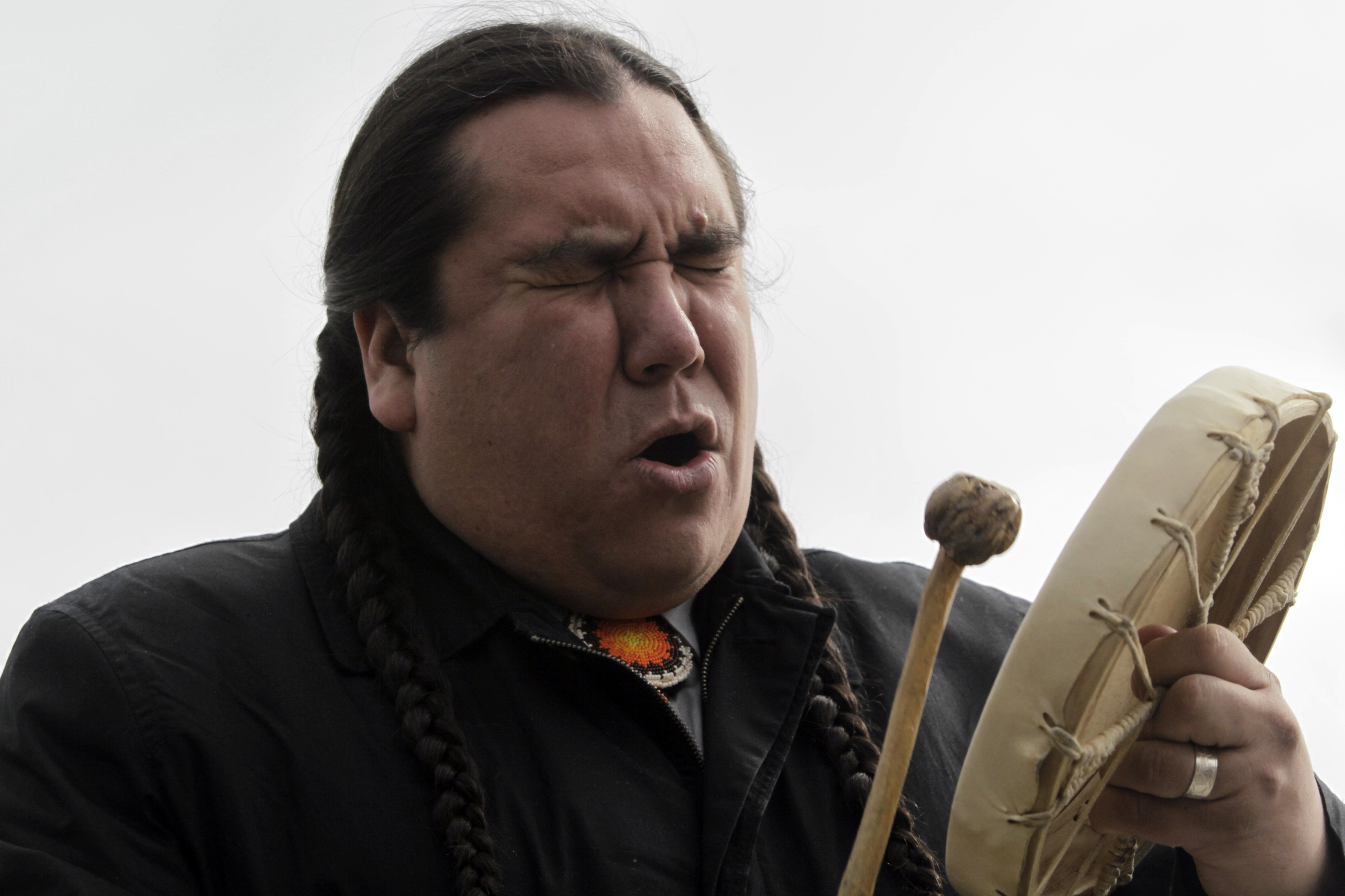 Clayton Thomas Mullen from the Indigenous Environmental Network in Canada, sings a traditional song during a protest against BP in London on April 14, 2011. (AP Photo/Lefteris Pitarakis)