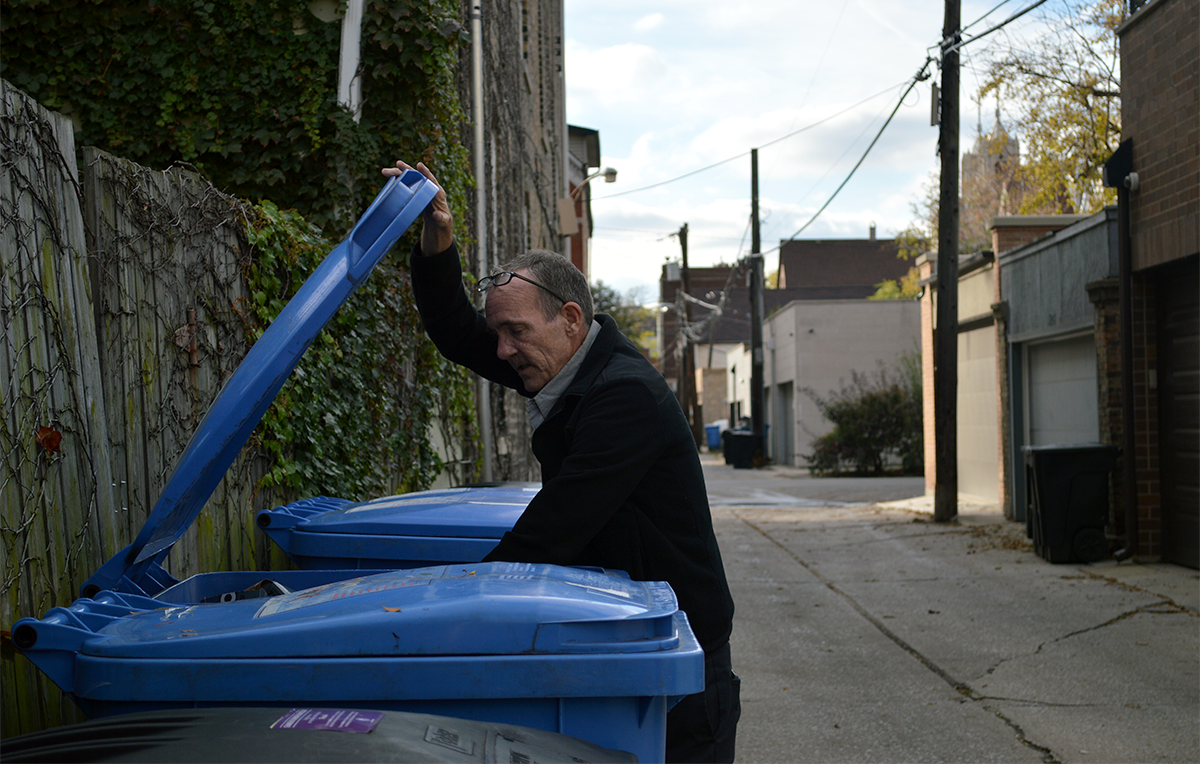 Scott Felgenhauer looks through recycling bins in his neighborhood, something he does regularly to keep the carts in his alley clean and organized. But even Felgenhauer's cart has gotten tagged with a sticker telling him the contents couldn't be recycled. (Max Green/WBEZ)