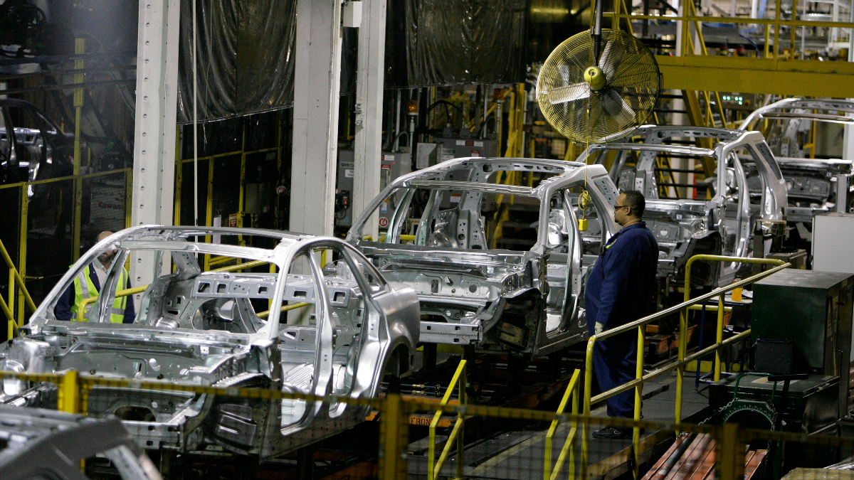 A Ford Motor Company employee watches chassis for the 2008 Ford Taurus, 2008 Ford Taurus X, and Mercury Sable roll by on the assembly line at the Chicago Assembly Plant where they were being built in June 2007. (AP Photo/M. Spencer Green)