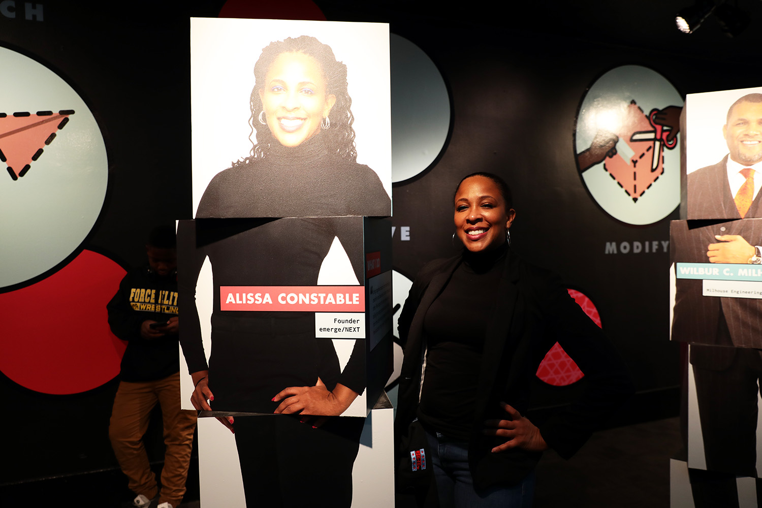 "Alissa Constable, founder of emerge/NEXT, stands next to her image at the Innovation Studio. Guests are greeted with images and video of Constable and Shala. Black Tech Mecca CEO Fabian Elliott, Sugar Gamers founder Keisha Howard, Milhouse Engineering and Construction Chairman and CEO Wilbur C. Milhouse III, Lighthouse Whole Food Grille founder and owner Erik ""Rico"" Nance, and Dr. Eric Whitaker, physician and investor at Chicago Area Health and Medical Careers program. (Arionne Nettles/WBEZ)"