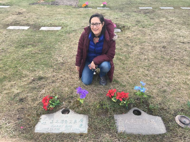 Monica Eng at the grave of her grandfather Harry Eng and grandmother Nora Sit Eng in the Chinese section of Mount Auburn Memorial Park in suburban Stickney, Illinois. (Katherine Nagasawa/WBEZ)