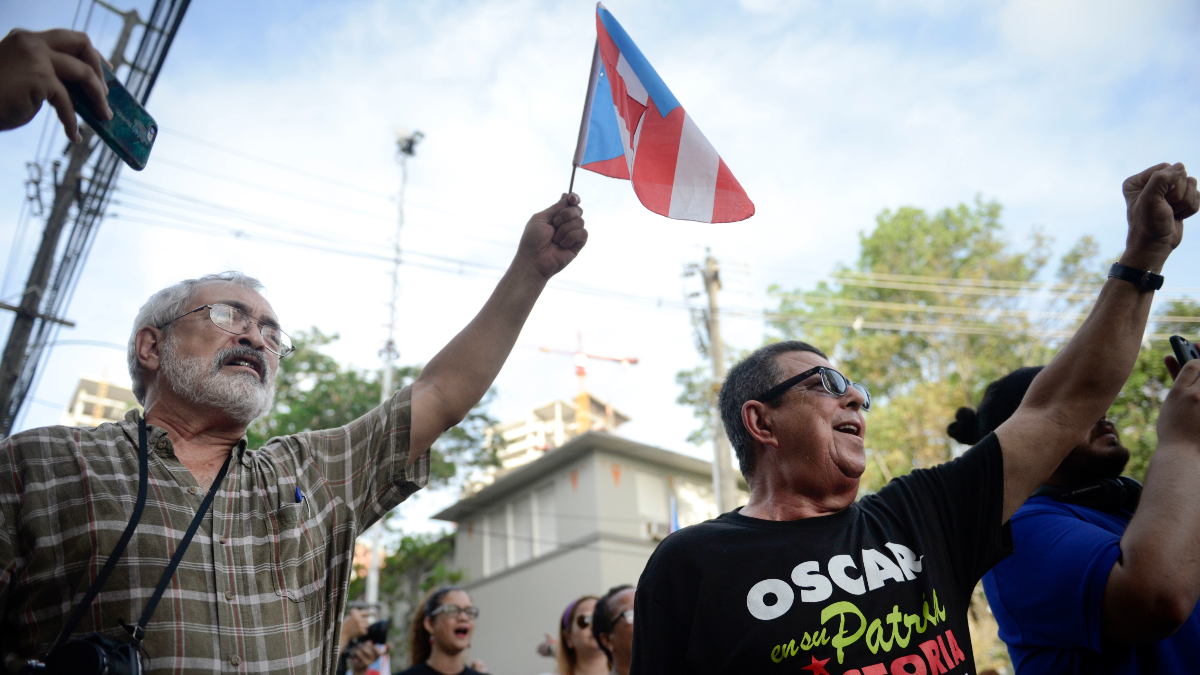 Supporters of Puerto Rican nationalist Oscar Lopez Rivera gesture as Rivera is released from home confinement after 36 years in federal custody, in San Juan, Puerto Rico, Wednesday, May 17, 2017. Lopez was considered a top leader of Puerto Rican militant group that said it was responsible for more than 100 bombings in several U.S. cities and Puerto Rico during the 1970s and early 1980s. (Carlos Giusti/AP)