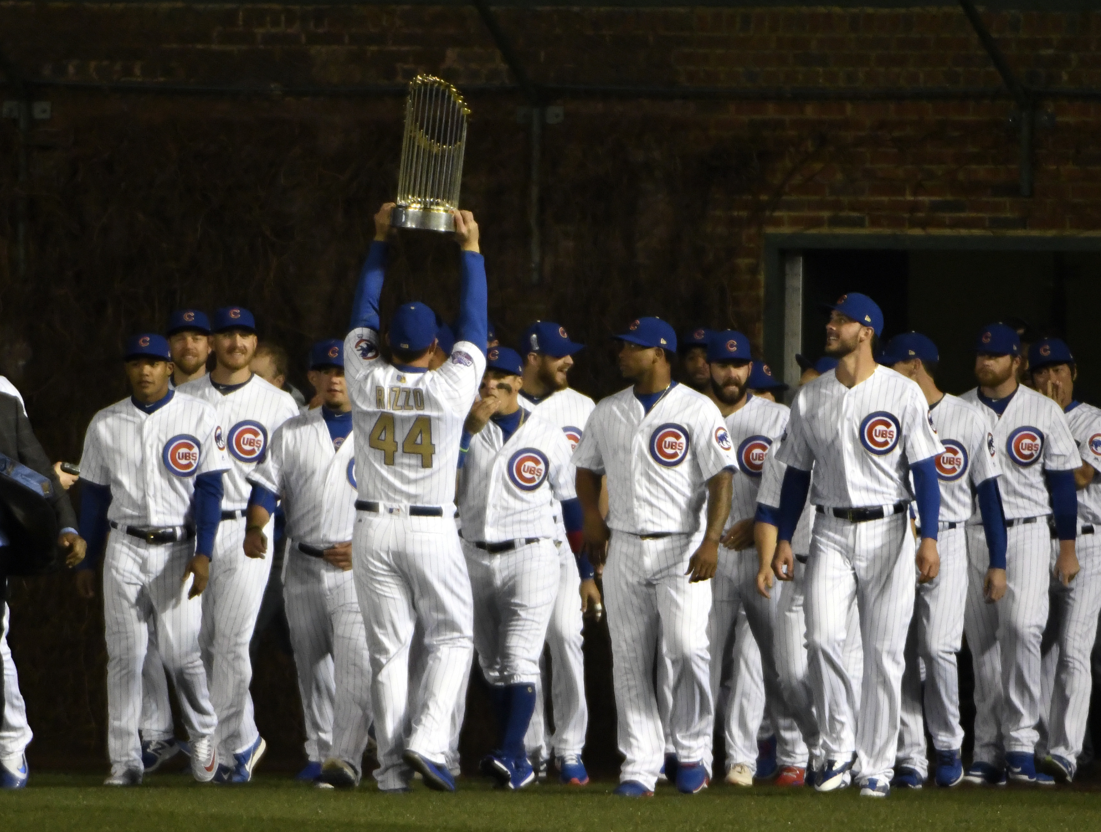 Cubs first baseman Anthony Rizzo (44) carries the 2016 World Series Championship trophy onto the field after the Cubs took turns raising the team's first championship banner in 108 years. (AP Photo/David Banks)