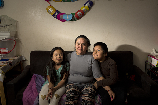 Domitila Valerio with her children, Esmeralda, 9, and Diego, 7, at their home in the Little Village neighborhood of Chicago.  (Michelle Kanaar for APM Reports)