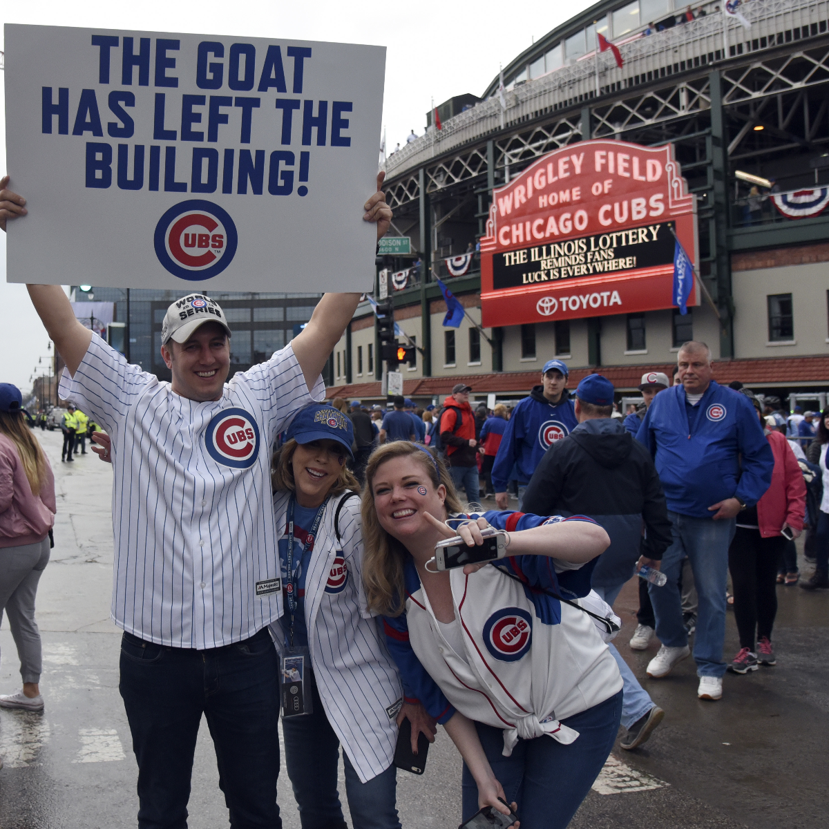 Dan Virgilio, left, Mary McSwain, center, and Elizabeth Roberts, right, hold a sign in front of Wrigley Field before the Cubs home opener. (AP Photo/David Banks)