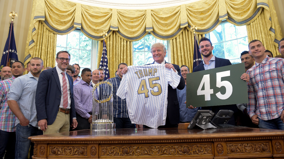 President Donald Trump holds up a Chicago Cubs jersey as he meets with members of the 2016 World Series Champions Chicago Cubs, Wednesday, June 28, 2017, in the Oval Office of the White House in Washington. Cubs third baseman Kris Bryant is at right. (Susan Walsh/AP)