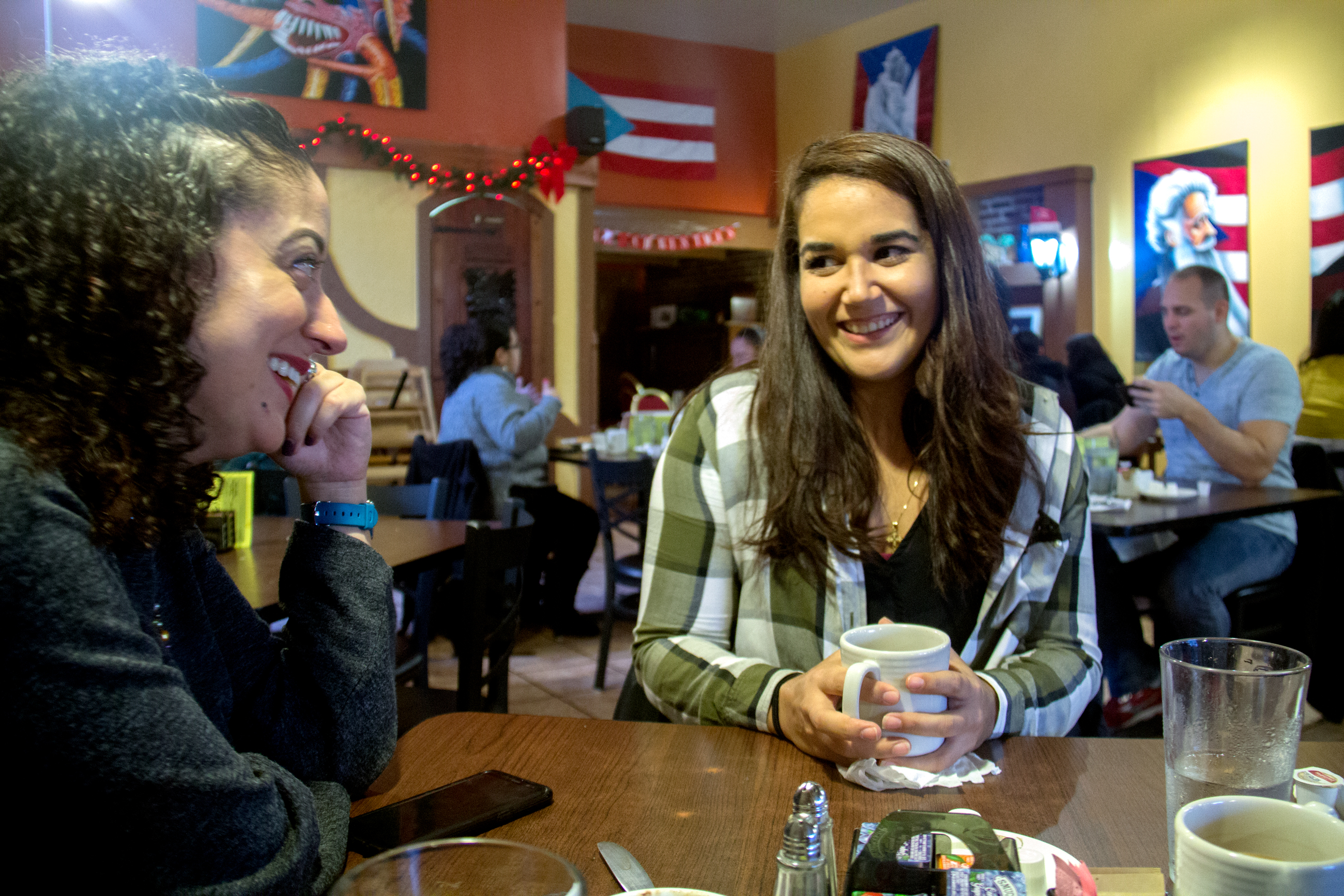 Yaira Rios (right) eats breakfast with her cousin, Natalia Delgado, recently at Nellie's Restaurant in Humboldt Park. (WBEZ/Lakeidra Chavis)