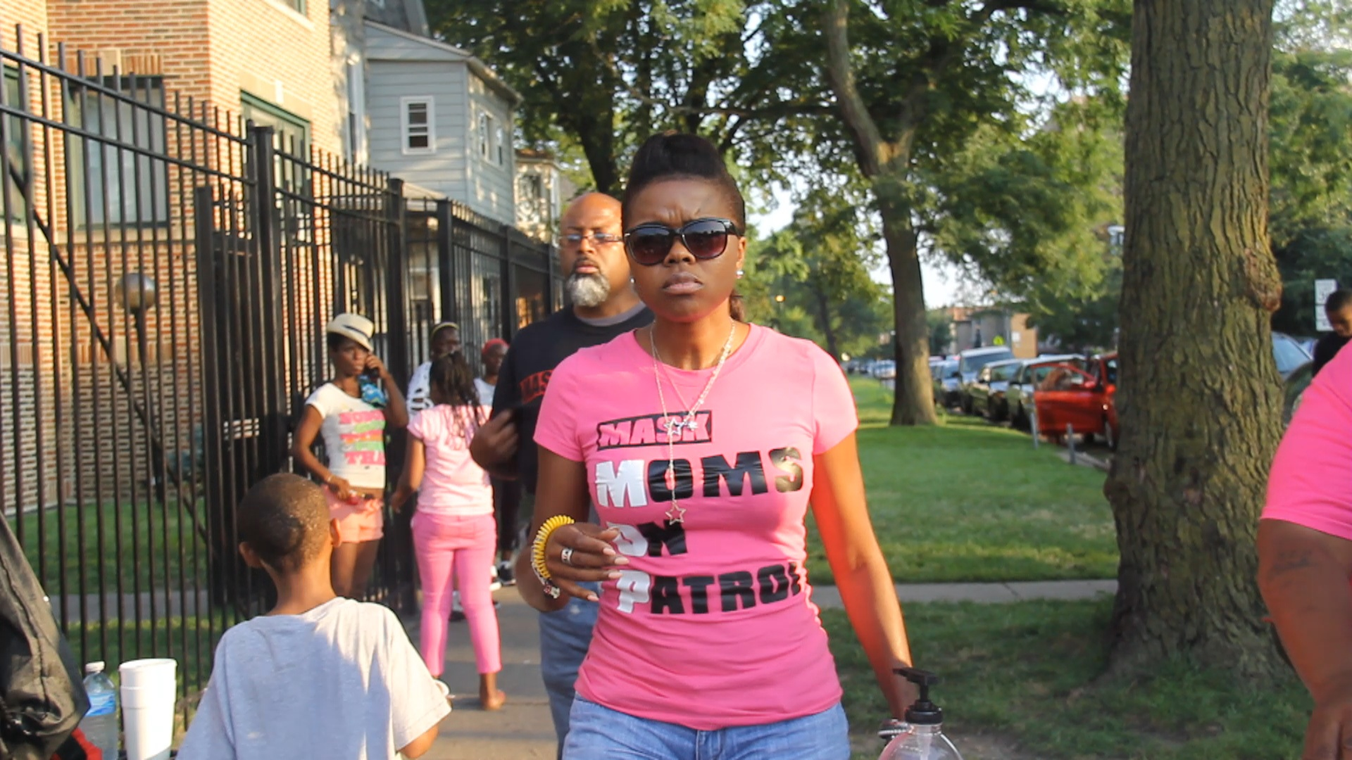 Tamar Manasseh walks down the street during a recent gathering. She started Mothers Against Senseless Killings last year to patrol the block of 75th and Stewart. (Andrew Gill/WBEZ)