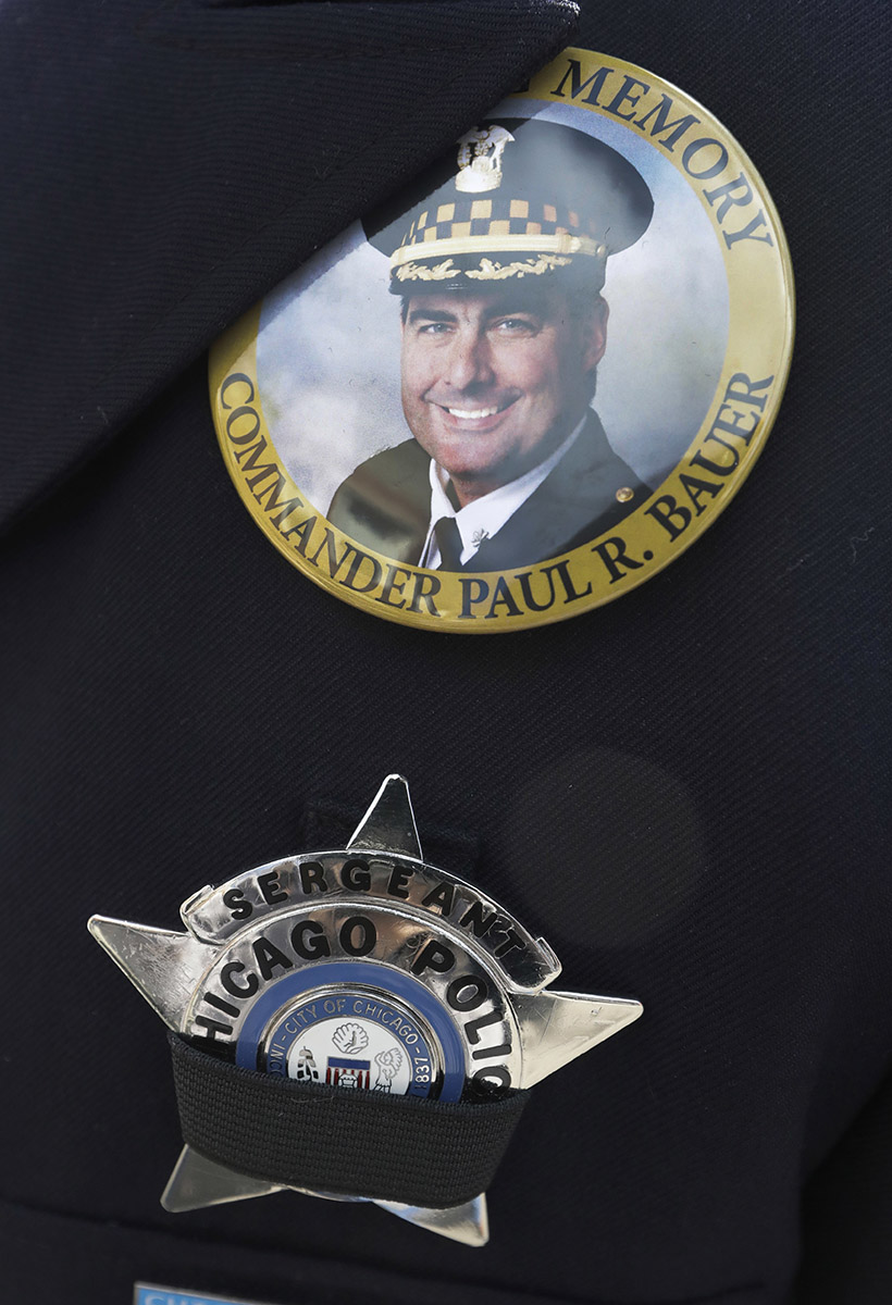 The badge of a Chicago police Sgt. Is covered with a black ribbon below a memorial button for Chicago Police Cmdr. Paul Bauer. (AP Photo/Charles Rex Arbogast)