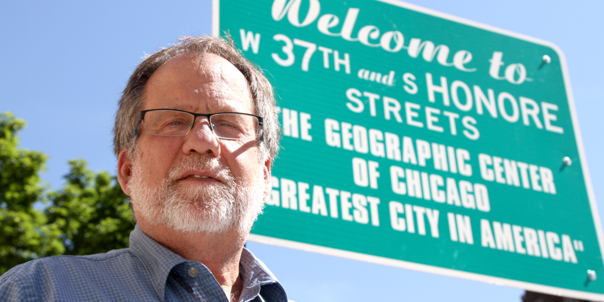 Pastor Doug Semenske of St. Andrew Lutheran Church stands in front of Chicago's center point sign, which sits just outside the church in the McKinley Park neighborhood. (Logan Jaffe/WBEZ)