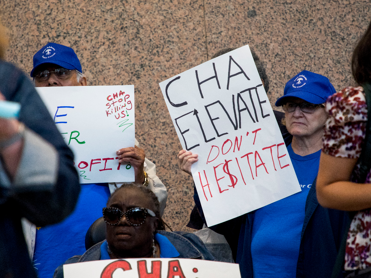 Seniors hold signs expressing their frustrations with CHA's elevators.(Paula Friedrich/WBEZ)