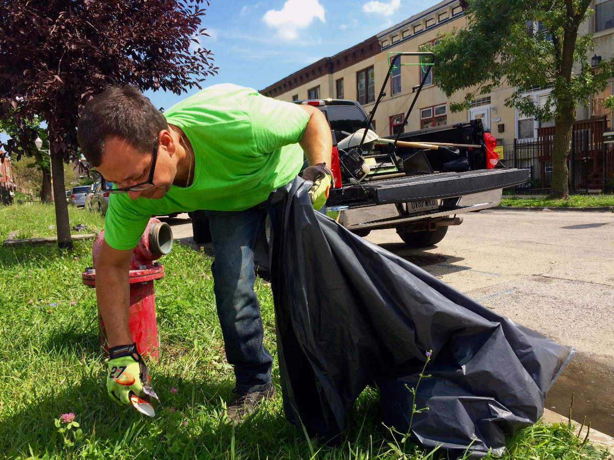Staniszewski grabs trash on a vacant lot owned through the city's Large Lots Program. He said he spends around 6 hours per week maintaining the properties.