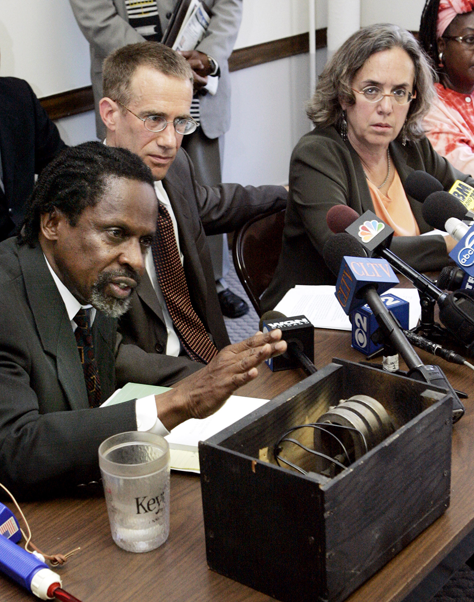 Attorney Standish E. Willis, left, speaks at a 2005 news conference in Chicago where attorneys and community activists gathered to ask international human rights monitors to intervene and investigate allegations that former Chicago Police Commander Lt. Jon Burge and others tortured suspects between 1971 and 1992. In the foregorund is a replica of one of Burge's alleged torture devices used to electrocute suspects during interrogations. (AP Photo/Charles Rex Arbogast)