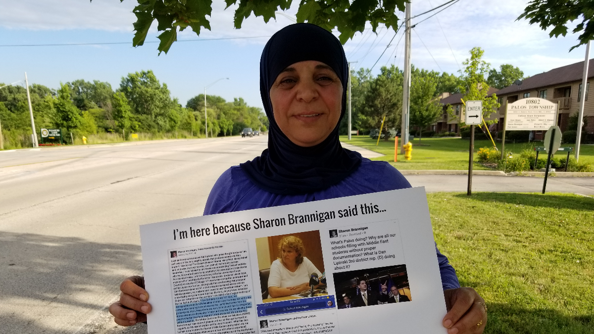 Manal Mohammad holds a protest sign for drivers to see from Roberts Road. She was one of about 100 protesters who gathered Monday to mark the one-year anniversary of their call for embattled Palos Township trustee Sharon Brannigan to resign. (Linda Lutton/WBEZ)