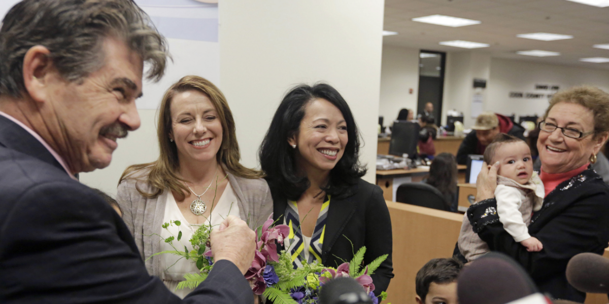 Cook County Clerk David Orr, left, performs a marriage ceremony for Theresa Volpe, second from left, and Mercedes Santos on Friday, Feb. 21, 2014, in Chicago. Same-sex couples in Illinois' Cook County began receiving marriage licenses immediately after a federal judge's ruling Friday that some attorneys could give county clerks statewide justification to also issue the documents right away. (AP Photo/M. Spencer Green)