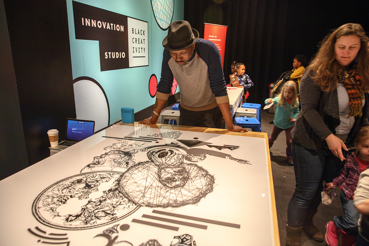 Chicago artists Shala. stands over his sketch that will sit in front of the collage. (Arionne Nettles/WBEZ)